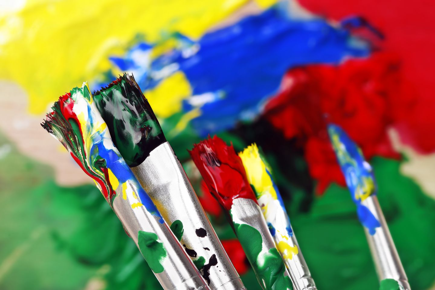 paint brushes with paint in front of colorful background